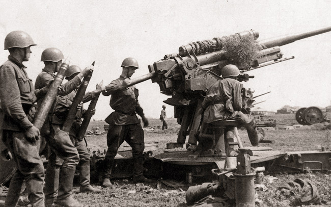 Расчет советского 76,2-мм зенитного орудия 3-К ведет огонь по наземным целям. На заднем плане видны стволы еще двух таких орудий  Источник — waralbum.ru - Немецкие танки у Волги | Военно-исторический портал Warspot.ru