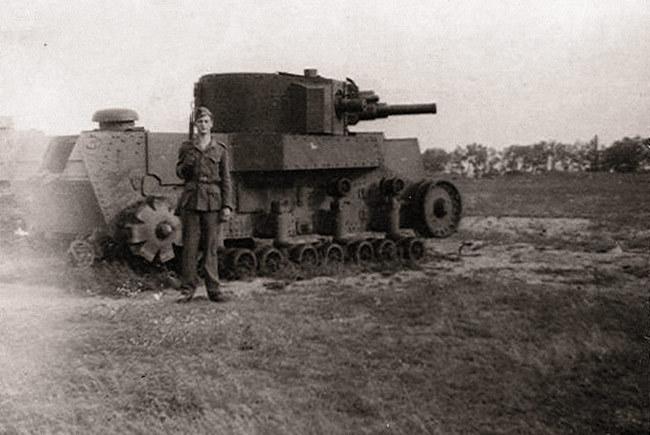 Немецкий солдат на фоне БОТа, в который был переделан танк Т-24, вооруженный 76-мм пушкой Л-10, Ленинградский ВО, осень 1941 года  Источник – aviarmor.ru -  Первый советский серийный танк | Военно-исторический портал Warspot.ru
