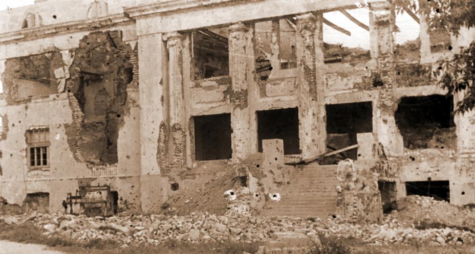 Западный фасад Драмтеатра, выходивший в Комсомольский сквер в сторону бункера ГКО. Здешним львам повезло гораздо меньше, чем их собратьям с центрального входа — они были расстреляны огнем пулеметов и самоходных орудий вместе с засевшими в здании бойцами дивизии НКВД. Неподалеку от этих львов умирал комиссар Щербина, а в подвале задыхались не желавшие сдаваться красноармейцы. Это место и происходившие рядом события могут «дать фору» иным шекспировским пьесам и невольно отсылают к мифу о могиле небезызвестного спартанского царя. - Неизвестный Сталинград:<br /> Городской сад   Военно-исторический портал Warspot.ru