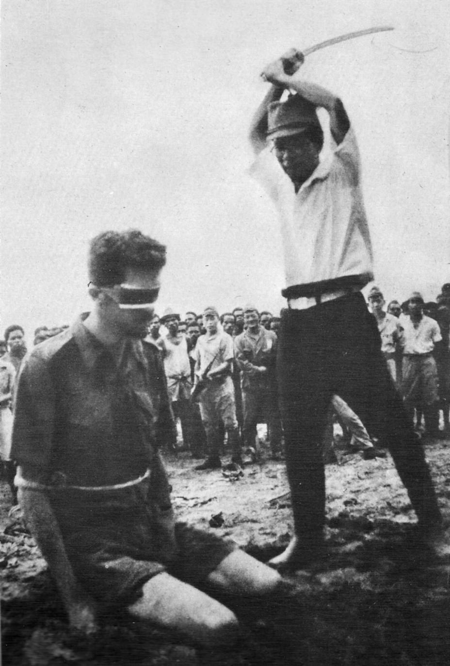 Эта шокирующая фотография, сделанная по просьбе палача, считается единственным достоверным снимком, запечатлевшим убийство пленных бойцов союзных войск Источник: awm.gov.au - «Безрассудный» десант Макартура | Военно-исторический портал Warspot.ru