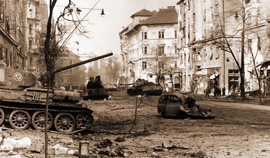 Та же группа танков, что и на предыдущих двух снимках, но с другого ракурса. На башне ближайшей «тридцатьчетвёрки», подбитой на выезде из арки дома, видны опознавательные знаки Венгерской Народной Армии, что с большой долей вероятности позволяет предположить, что танк использовался мятежниками - Будапешт-1956: танки против танков | Военно-исторический портал Warspot.ru