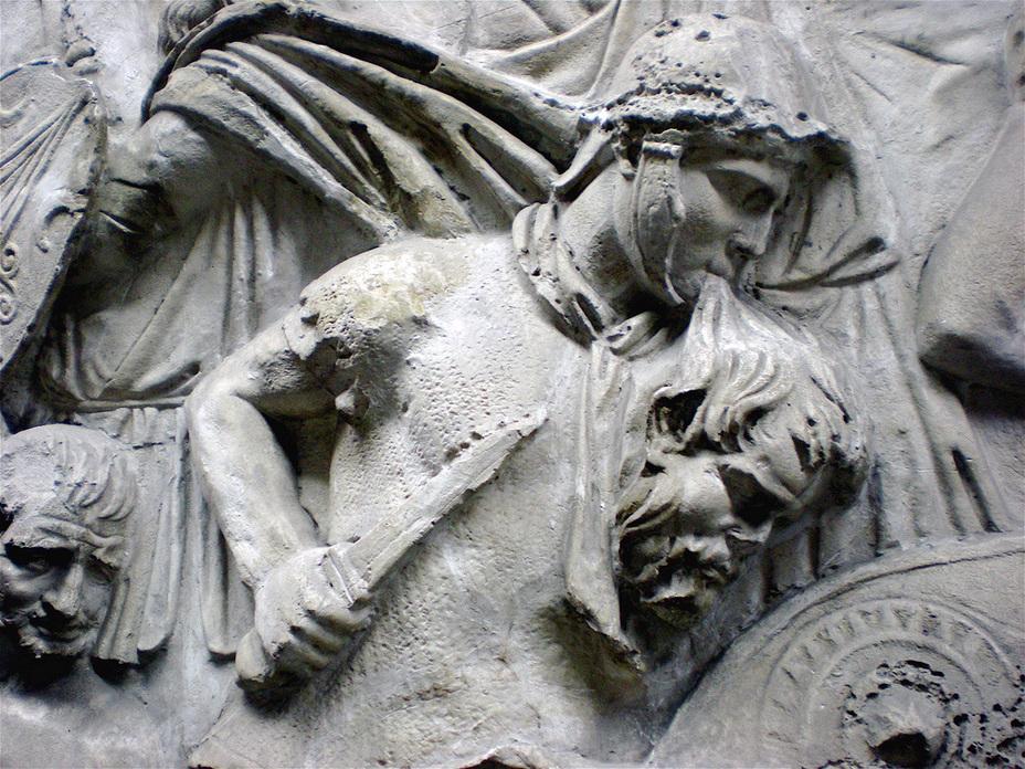 Шокирующая своим натурализмом сцена с рельефа Колонны Траяна: римский воин в зубах держит отрубленную голову, в то время как его руки заняты оружием