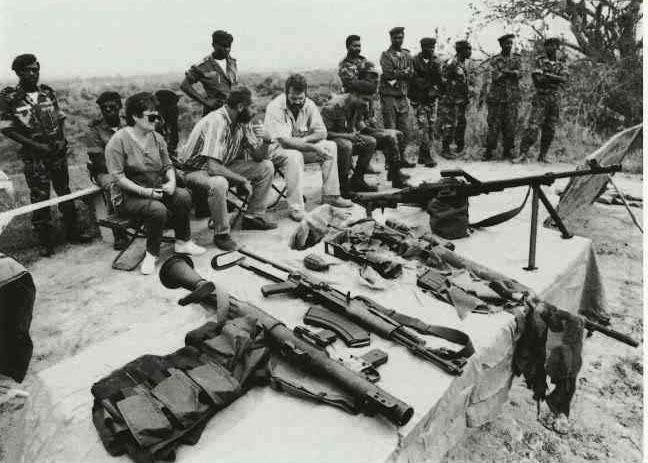Сотрудники Executive Outcomes в присутствии командиров ангольской армии демонстрируют захваченное у мятежников оружие. Лагерь на Рио Лонга