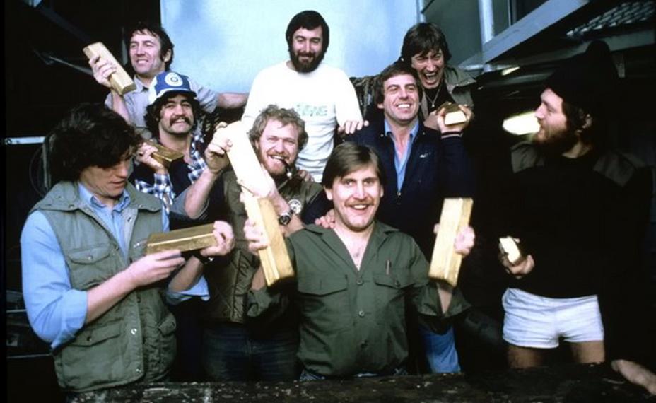 Члены экспедиции по подъему сокровищ «Эдинбурга» позируют с золотыми слитками после успешного завершения работ