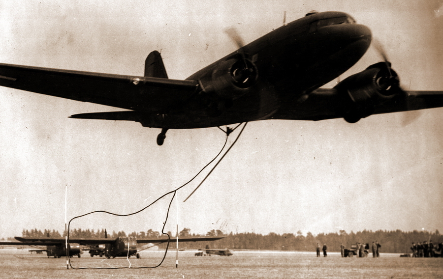 Военно-транспортный «Дуглас» C-47 подхватывает стоящий наискось от «ворот» десантный планер «Вако» CG-4