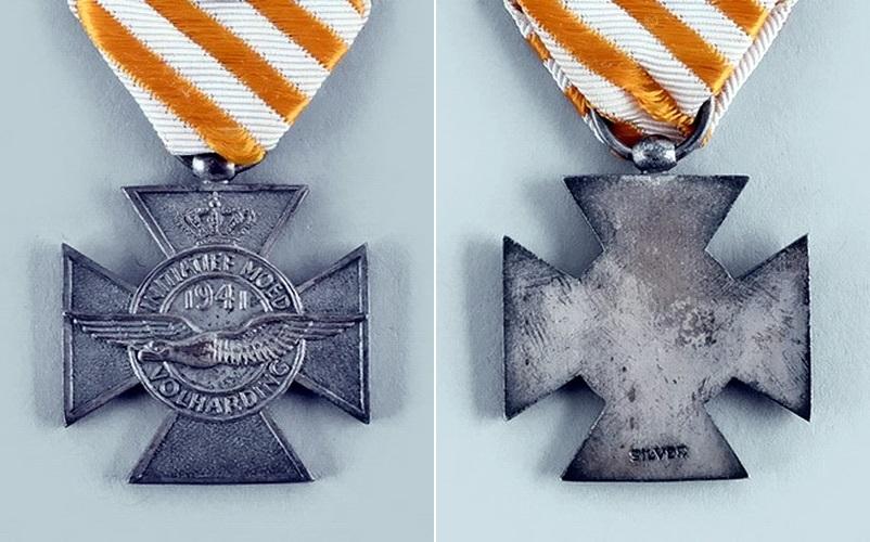 Крест размерами 30,5×30,5 мм изготавливается из серебра. В увенчанном королевской короной медальоне помещён летящий альбатрос, сопровождаемый датой «1941» и девизом «Инициатива, смелость, настойчивость» (Initiatief, Moed, Volharding). Реверс креста гладкий. Муаровая лента креста шириной 27 мм образована чередующимися под углом 45° золотисто-оранжевыми и белыми полосками шириной 2,7 мм. Повторные награждения отмечаются металлическими цифрами «2» и «3» на ленте, там же в годы войны иногда носилась миниатюрная корона как знак упоминания в приказе - Warspot о наградах: серебряный крест «Оранжевого солдата» | Warspot.ru