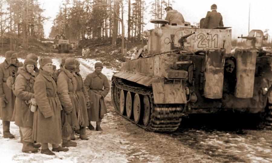 Колонна «Тигров» 501-го тяжёлого танкового батальона проезжает мимо группы советских военнопленных. На корме машины установлены два трофейных станковых пулемёта ДС-39 - Наступление в «медвежьем углу» | Warspot.ru